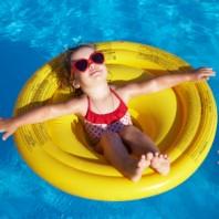 Bimba in piscina su un canottino giallo