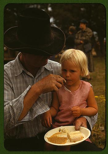 Un padre offre un pezzo di torta alla figlia piccola